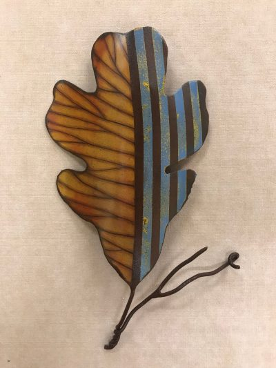 A leaf sculpture made of recycled metals. A deep orange colored design on the left half of the leaf, and a blue and brown striped design on the right.