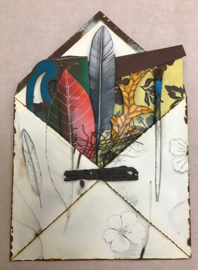 wall hanging metal sculpture of an open envelope filled with various items. Items include, three different leaves, a paint brush, wire material. Pencil drawings also on the outside of the envelope.