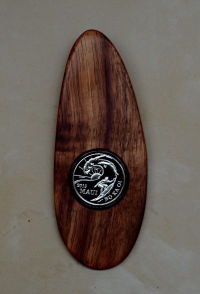 an ornament made of local Hawaiian Koa wood, shaped like a surfboard, with a 2015 trade dollar inlay-ed in the center