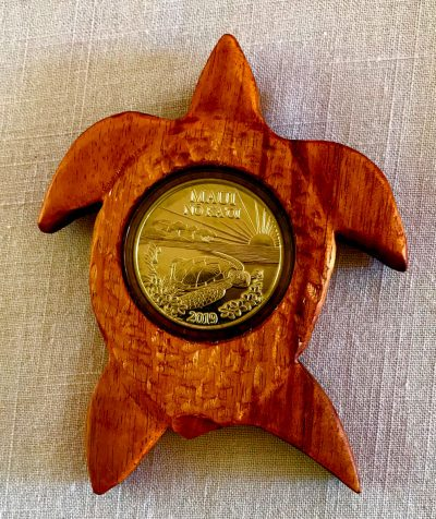 an ornament made of local Hawaiian woods, shaped like a turtle, with a 2019 trade dollar inlay-ed in the center