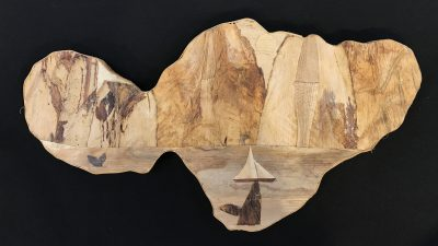 Maui island wall hanging from the mind of Baz Cumberbatch. He carves the background from wood, then adds layers of natural fibers by hand